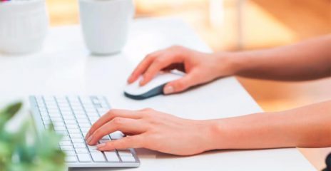 A woman's hands at a desk using a keyboard and mouse.