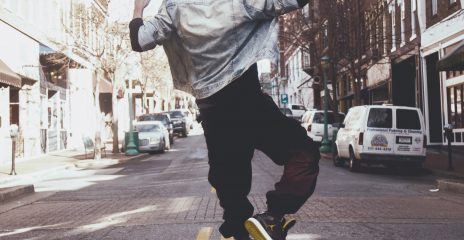 A man in a street jumps with his hands in the air.