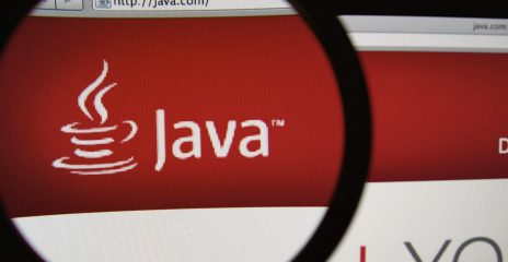 A magnifying glass over a computer screen with the Java Logo enlarged.