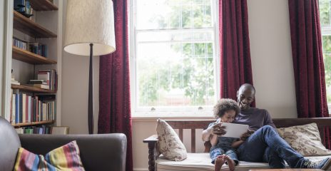 A man and a daughter sit in their living room smiling and holding a tablet together.