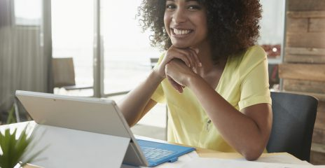 A woman sits and smiles in front of her tablet computer.