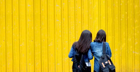 Two women in dark blue outfits stand in front of a bright yellow metal wall, they are looking down at something together.