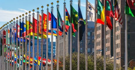 A row of flags representing each country flap in the wind outside of the United Nations headquarters in New York City.