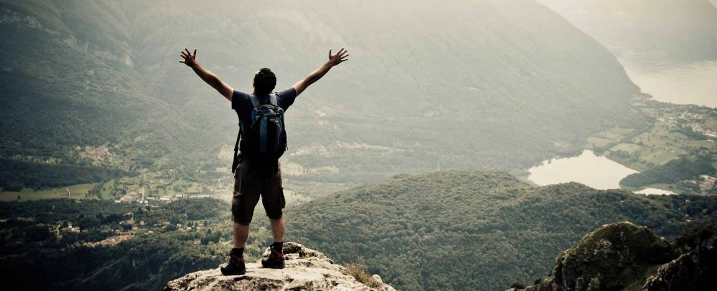 A man with his arms stretched out on top of a vista overlooking a valley.