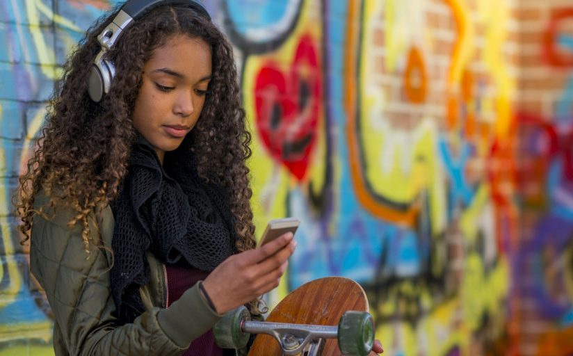 A young woman with a skateboard and headphones on browses content on her phone in front of a backdrop of graffiti.
