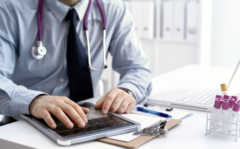A doctor sitting at his desk interacting with his tablet computer, with a clipboard, beakers, and a laptop.