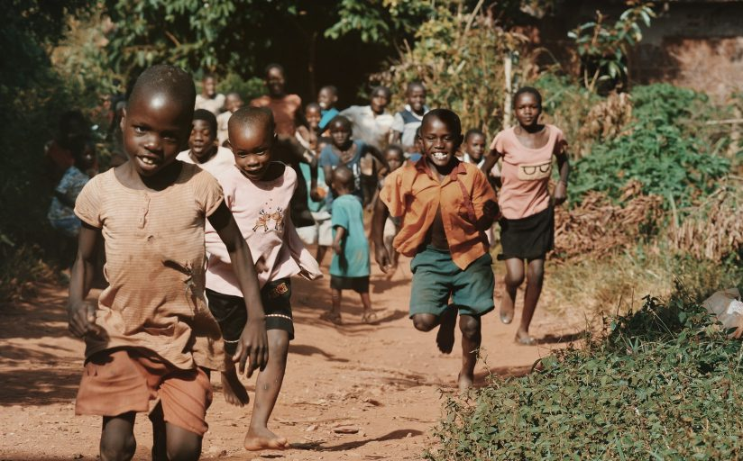 A group of children in Africa running and smiling along a path.
