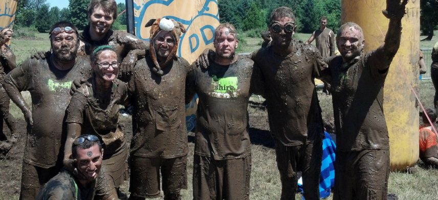 Concentric Sky employees after a mud race, smiling and covered in mud.