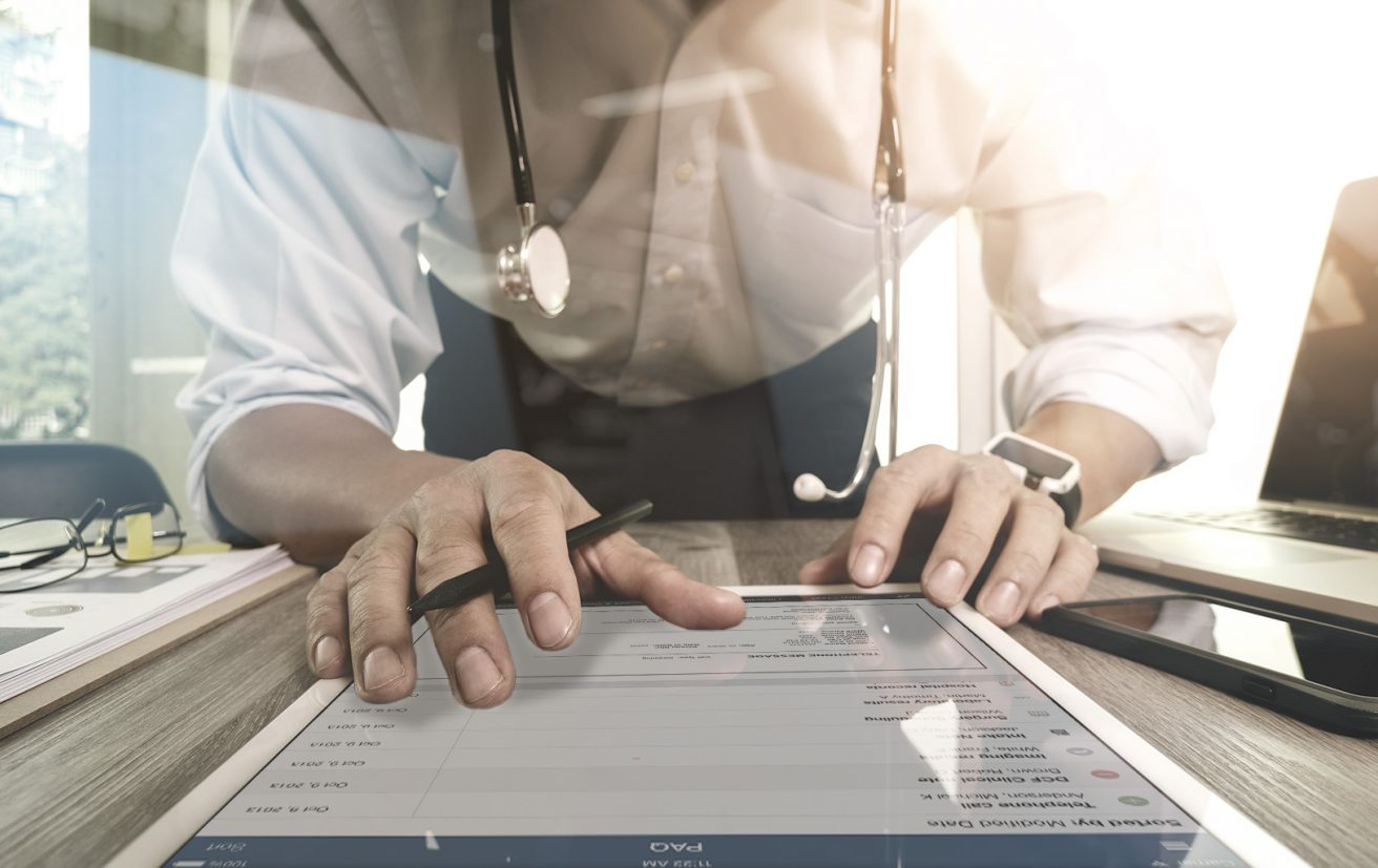 A doctor interacts with medical records on a tablet.
