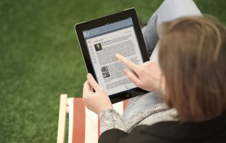 A woman uses the digital version of Encyclopedia Britannica on her tablet outside.