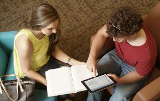 Two students sitting and studying together reading a book and the digital version of Encyclopedia Britannica on a tablet.
