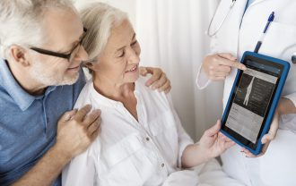 A doctor presents medical information on a tablet to a smiling patient and her husband.
